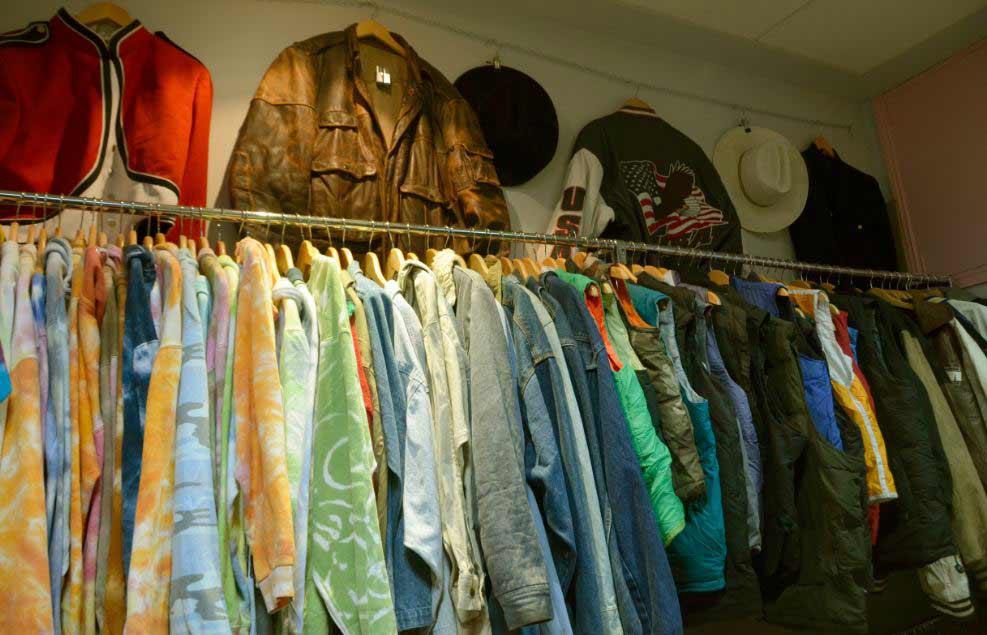 ropa de segunda mano por dentro, muchas chaquetas y camisetas colgadas