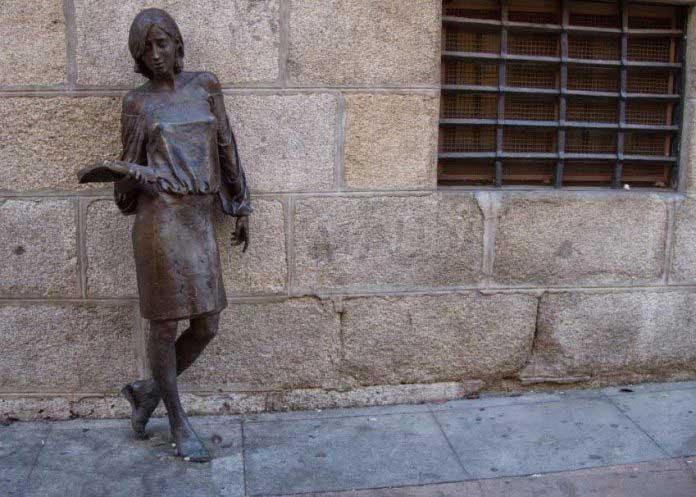 escultura de una mujer apoyada en la pared y una ventana con rejas