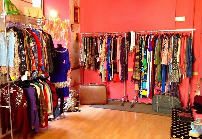 Interior de una tienda de ropa vintage, ropa de diferentes colores colgada