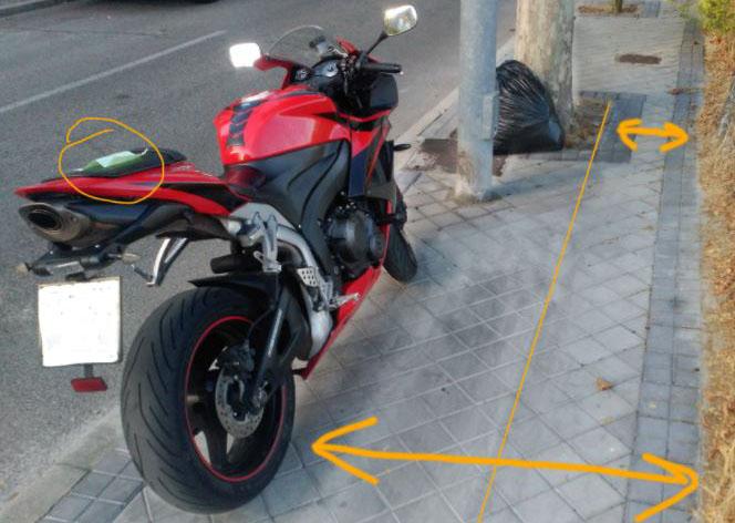 moto negra y roja estacionada en una acera con flechas indicando distancias