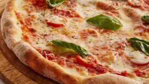 Pizza en primer plano de queso con hojas de albahaca por encima