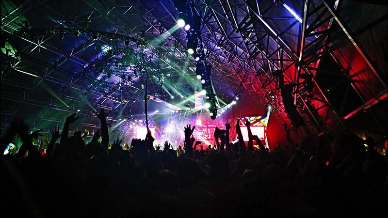 Mucha gente en un concierto con luces de colores y manos levantadas