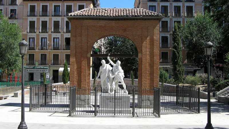 detalles de la plaza, escultura y arco de ladrillo