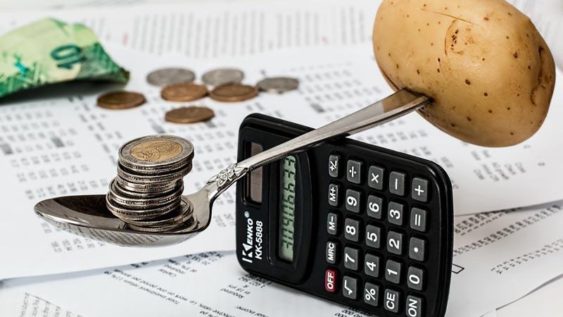 calculadora funcionando como puente de equilibrio entre una patata y un grupo de monedas