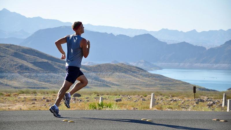 hombre corriendo por un paisaje montañoso y con un lago