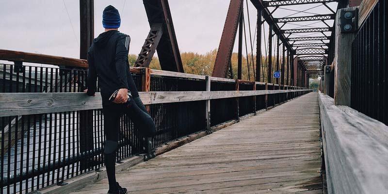 hombre calentando antes de correr a la entrada de un puente