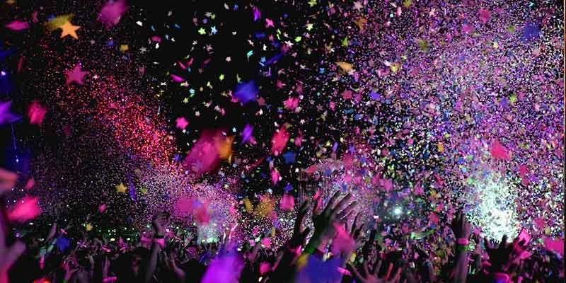 Confeti lanzado en un concierto y brazos intentado cogerlo