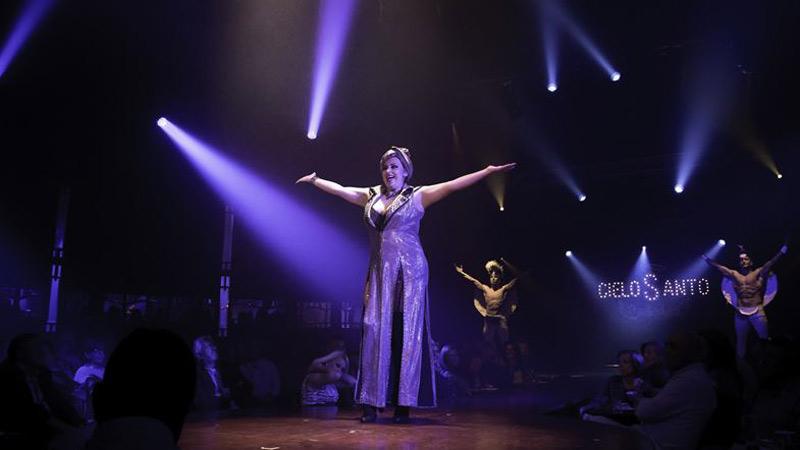 actriz frente al micrófono en la escena de la obra