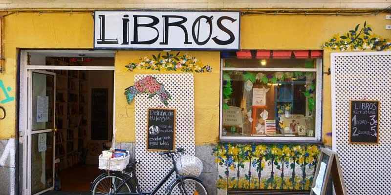 Fachada de la librería 'Libros para un mundo mejor' con una bicicleta en la entrada