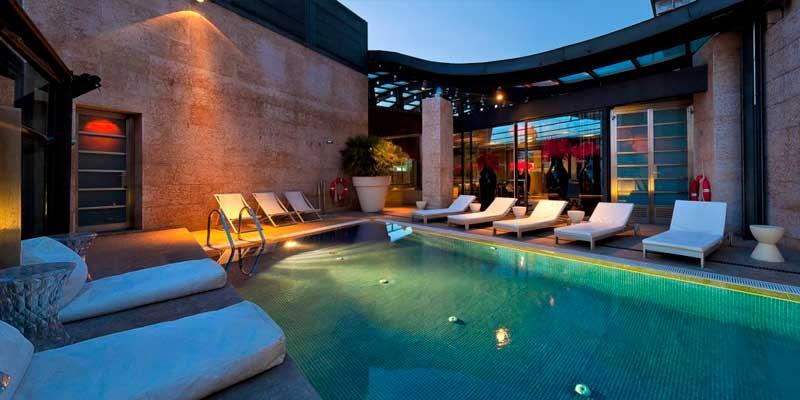 piscina, con bancos y camas alrededor de la Terraza del Urban