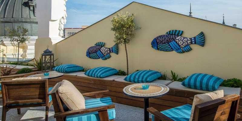 área de la terraza madrileña de The Mint decorada con peces y cojines azules