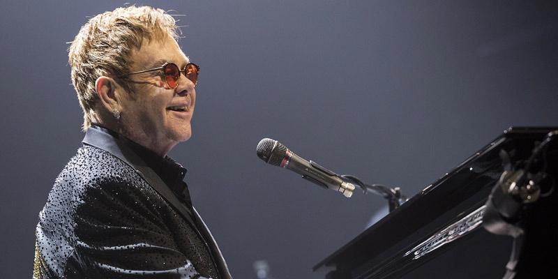 Elton John con gafas rojas con un micrófono y tocando el piano