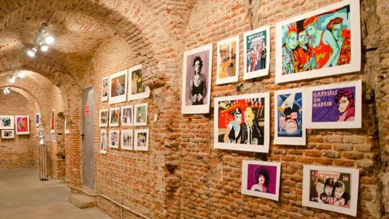 pared de una galería con cuadros expuestos sobre el punk