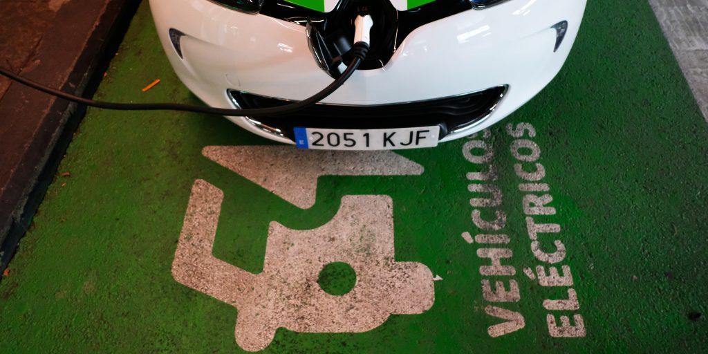 coche eléctrico cargándose y texto en el suelo