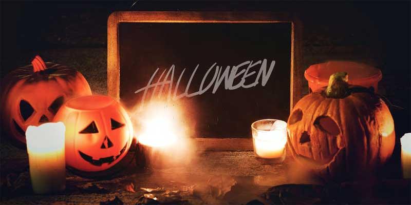 Cartel con Halloween escrito y calabazas talladas y velas