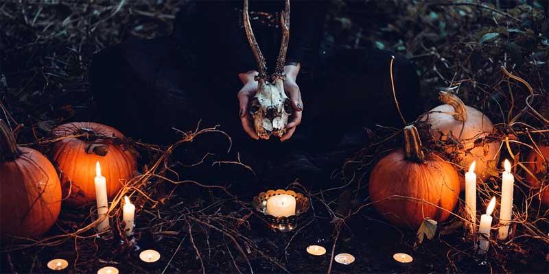Mujer arrodillada con una calavera, velas y calabazas
