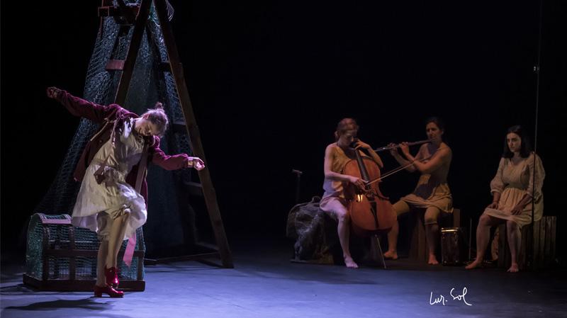 Mientras una mujer baila otras tres tocan unos instrumentos.