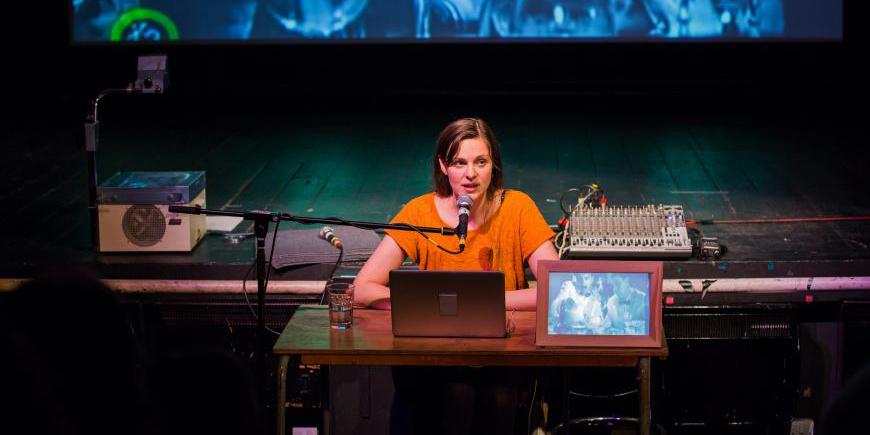 Deborah Pearson hablando en una mesa con un ordenador