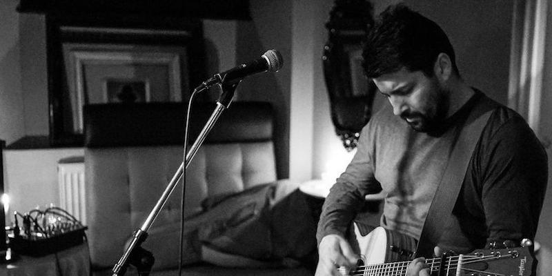 Ed Curtis tocando la guitarra en un salón con un micrófono delante