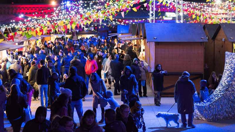 Mercado navideño lleno de gente y luces en Matadero