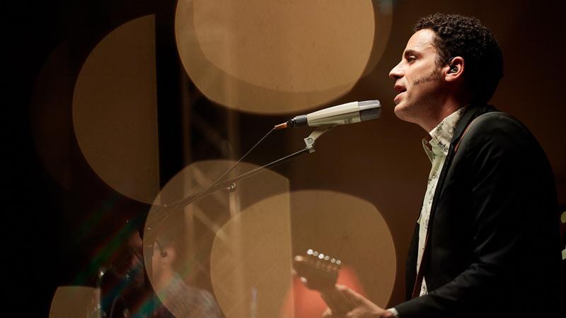 DePedro cantando en un concierto acompañado de su guitarra