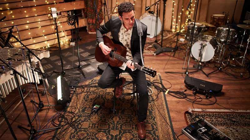 DePedro tocando la guitarra en el estudio