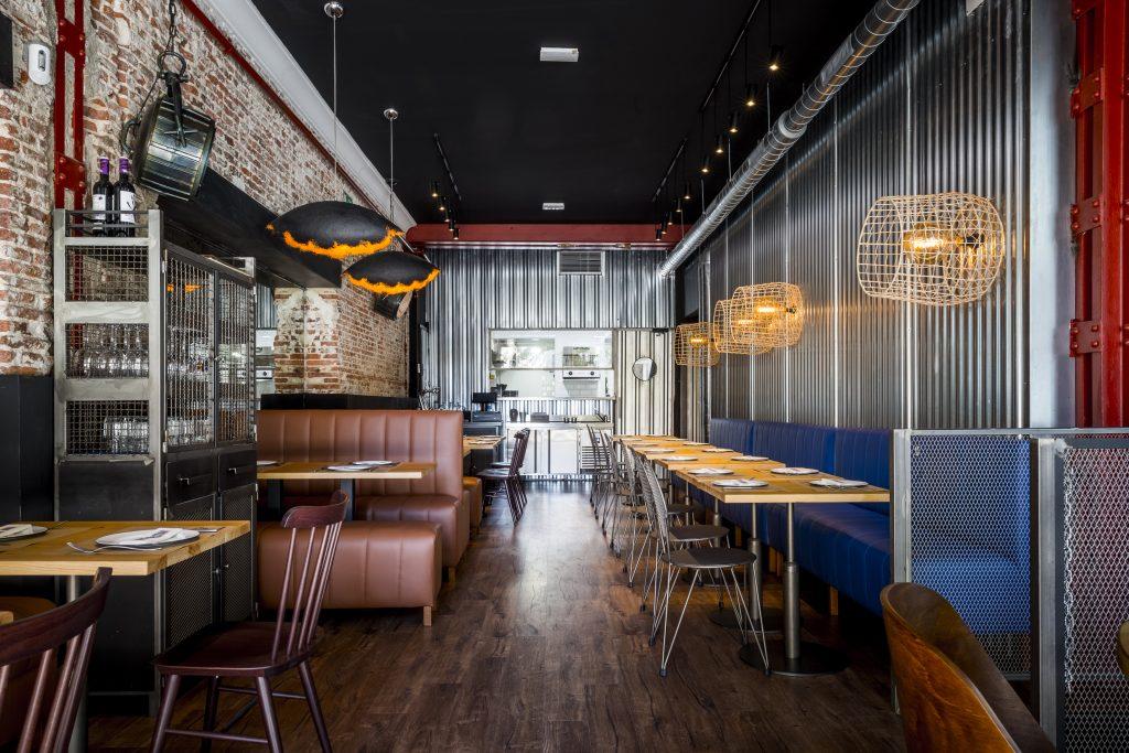 Interior del restaurante The Lobstar, en el que destaca la madera, presente en las mesas, sillas y en el suelo. La pared es de ladrillo y el techo alto y negro. Los focos de luz recuerdan a los de los barcos pesqueros.