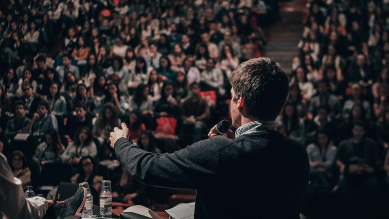 Ponente hablando a una multitud en una mesa de debate