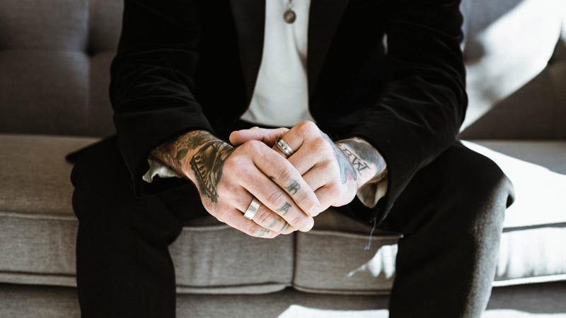 Hombre en traje con las manos tatuadas
