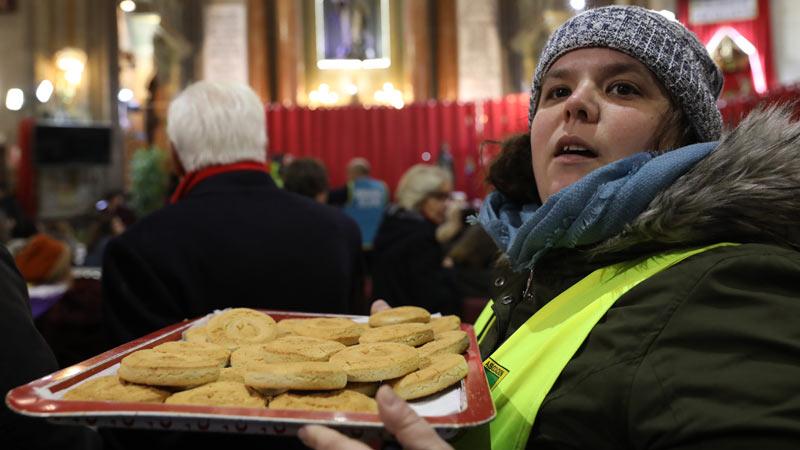 Mujer llevando una bandeja de panecillos de San Antón en la iglesia