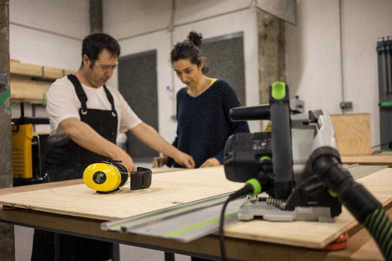 Chica enseñando a chico como trabajar la madera