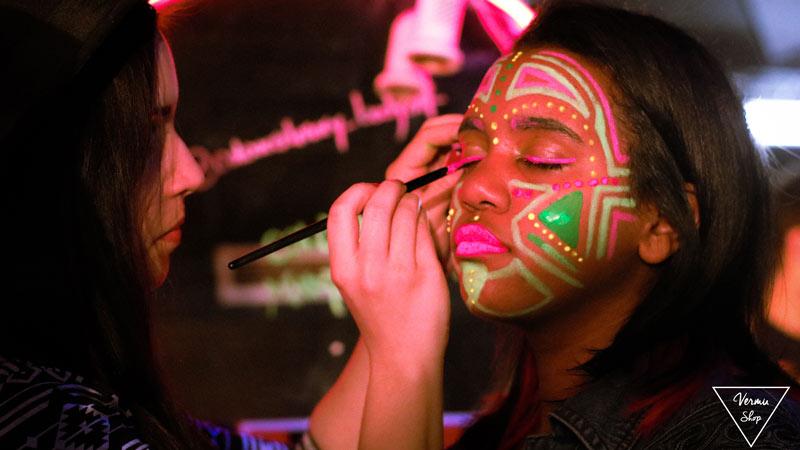 Chica haciéndole pinturas florescentes en la cara a otra chica