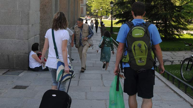 Turistas llevando maletas en el Paseo del Prado