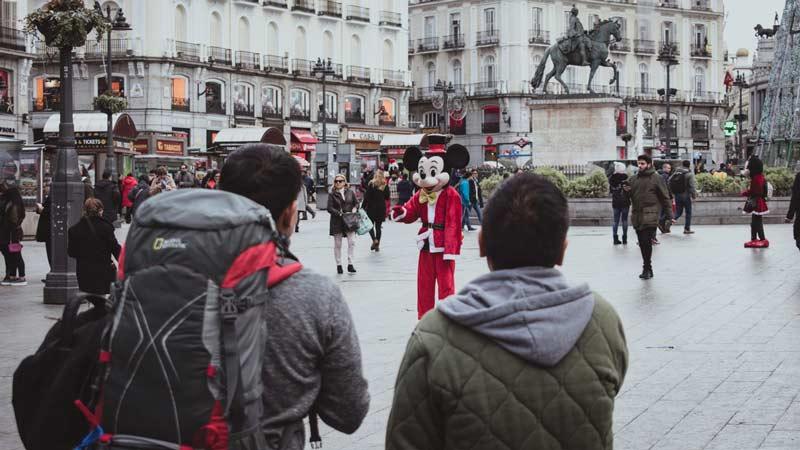 Pareja de turistas en la plaza de Sol en Madrid mirando a un personaje de dibujos
