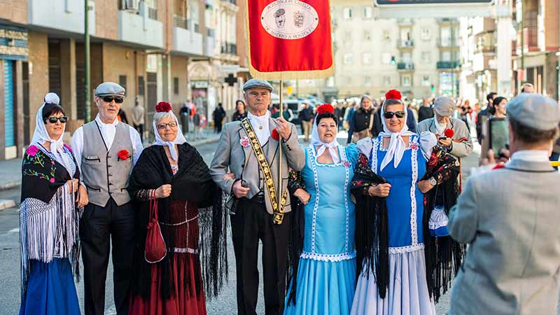 Grupo de gente mayor vestidos de chulapas y chulapos en medio de la calle haciéndose una foto con un móvil