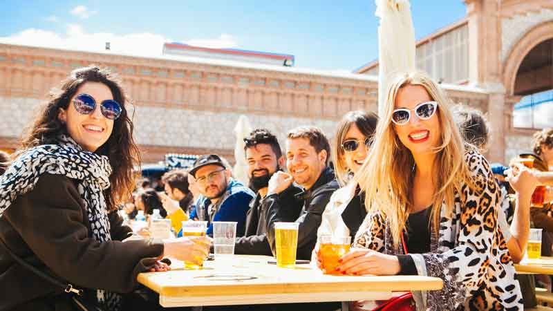 Grupo de amigos comiendo y bebiendo en las mesas junto a los food trucks