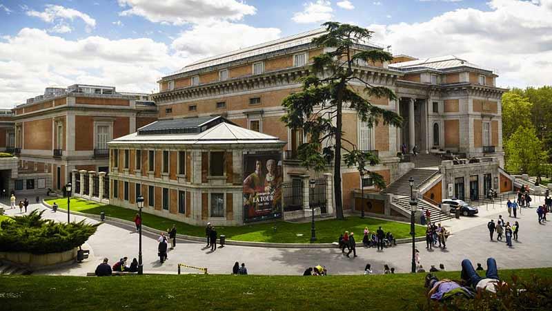 Visión general del museo del Prado desde el lado izquierdo, dos personas tumbadas en el césped
