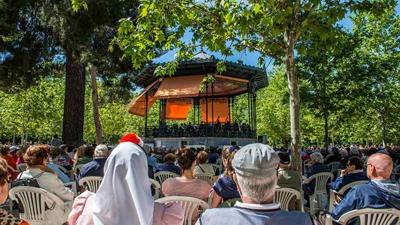 Concierto de la orquesta sinfónica en el parque de las vistillas, una pareja vestida de chulapos y chulapas en el centro, todos los asientos están llenos
