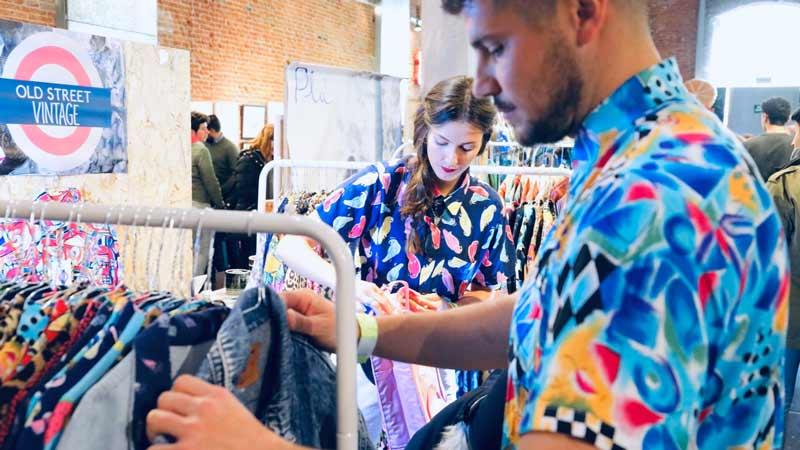 Un chico y una chica colocando ropa en un puesto vintage