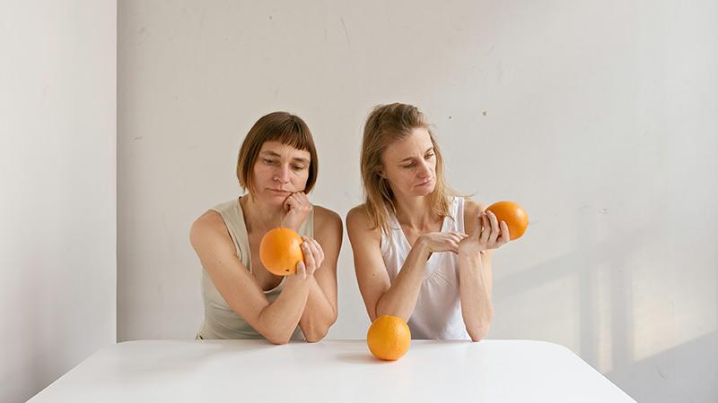 Obra de Elina Brotherus donde pueden verse a dos mujeres mirando tres naranjas sobre un fondo blanco