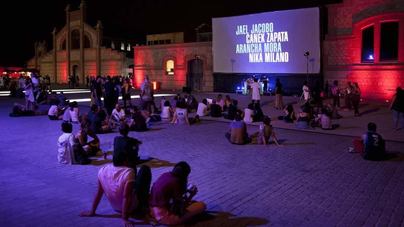 Gente sentada en un patio de Matadero disfrutando de los cortometrajes de la 1ª edición de ANIMARIO
