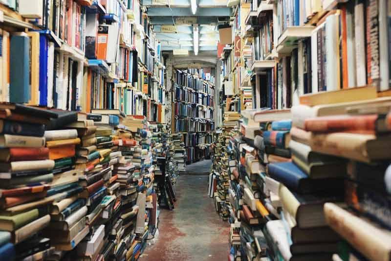 Pasillo de una librería con muchos libros apilados.