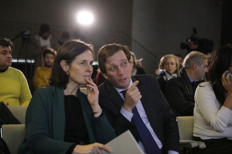 Un hombre y una mujer hablando mientras están sentados y el hombre apuntando a algo con el dedo.