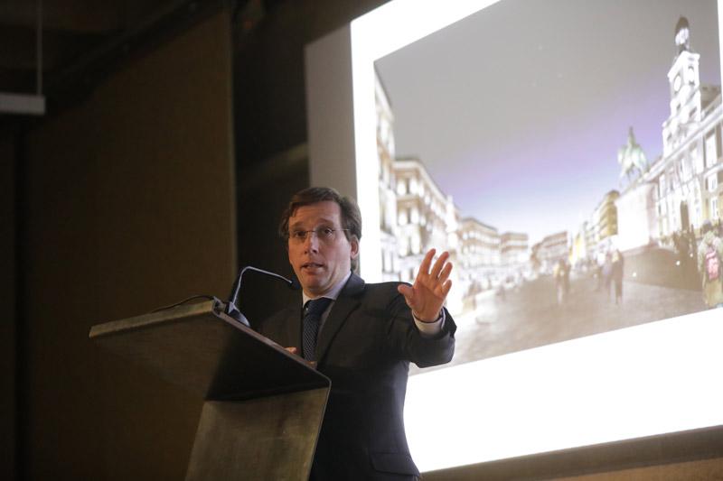 Un hombre hablando en un atril delante de un proyector.