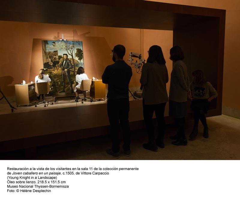 Varias personas viendo en el Museo Thyssen la restauración del cuadro 'Joven caballero en un paisaje' de Carpaccio