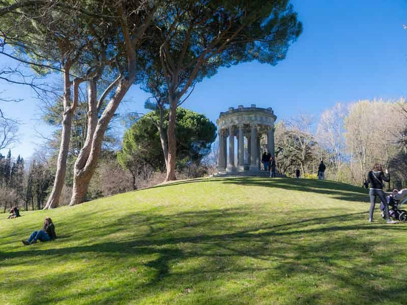 Monumento en un parque de Madrid, rodeado de árboles.