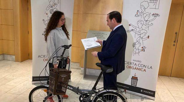Un hombre le entrega un diploma y una bicicleta a una niña.