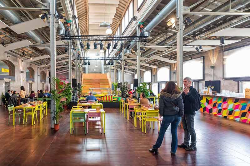 Foto del Café Naves en el que se ven muchas mesas, plantas, una grada y una barra.