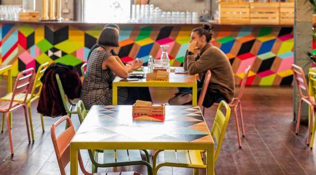 Dos personas sentadas en una mesa de una cafetería.