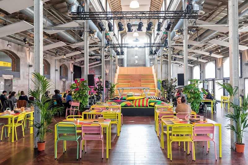 Café Naves en el que se ven muchas mesas muy coloridas, plantas y una grada al fondo.